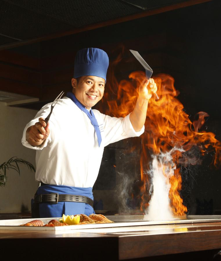 Tanaka+of+Tokyo+Chef+does+an+elaborate+fire+trick+while+grilling+up+food+for+guests.+