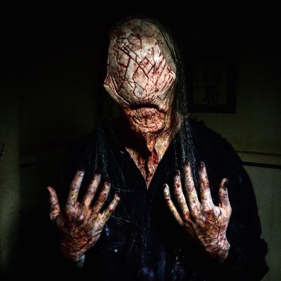A Faceless man with bloody scars waits to scare visiters as they enter the haunted house.