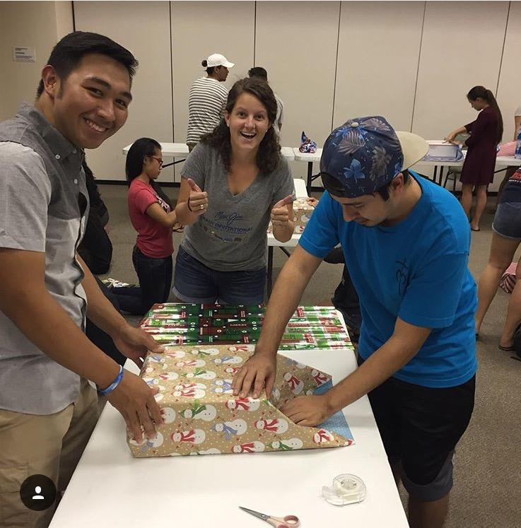 Student volunteers help prepare for Christmas on Campus by wrapping presents for the children.