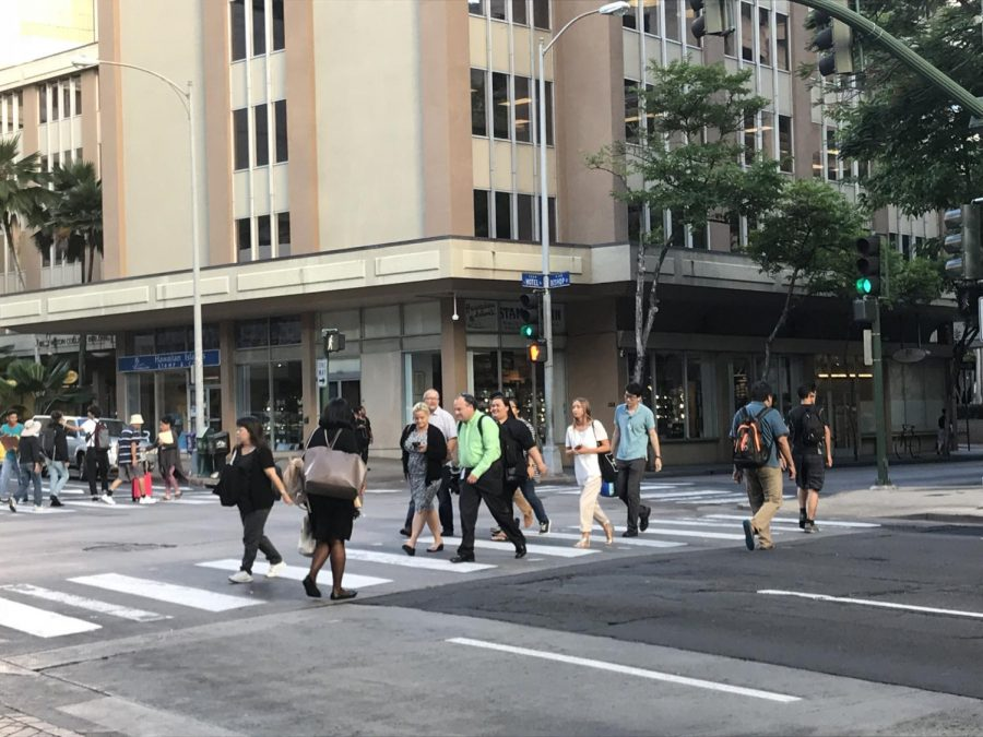 Pedestrians crossing at a crosswalk in downtown Honolulu. One pedestrian is spotted with an electric device, as if she's texting.