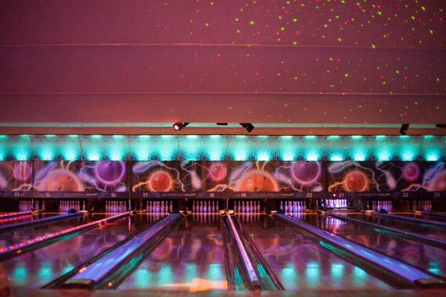 Bright lights and neon colors reflect along the lanes at the bowling alley.