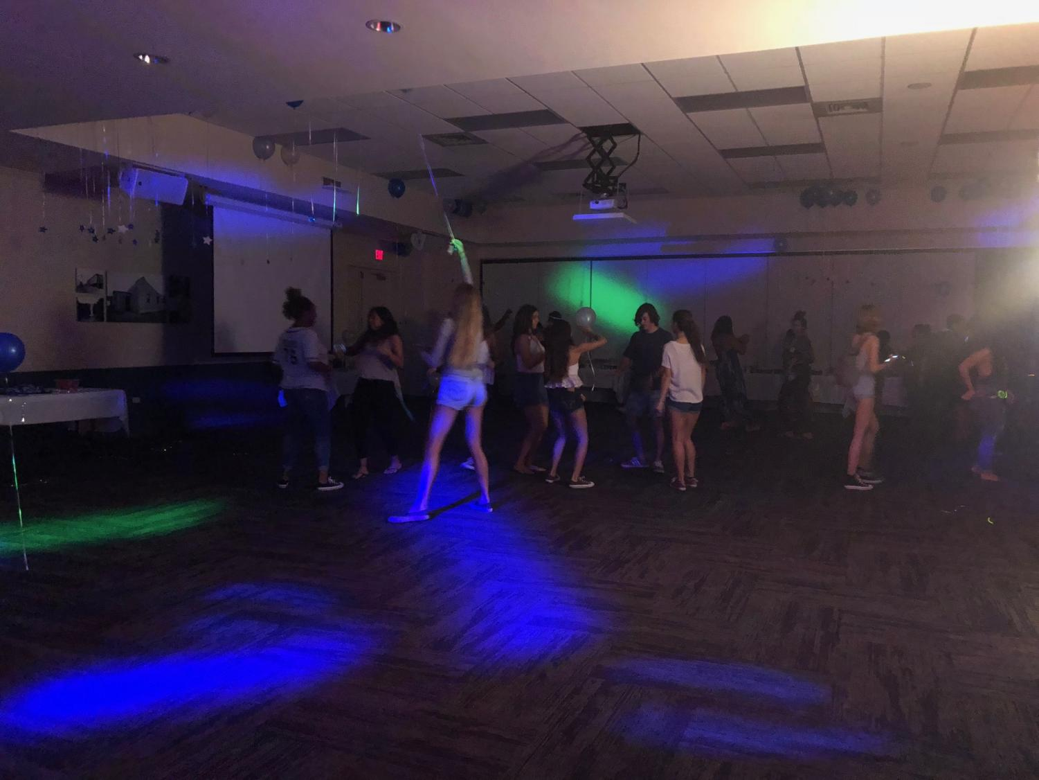 Students express their creative dance styles while neon lights flash across the room.