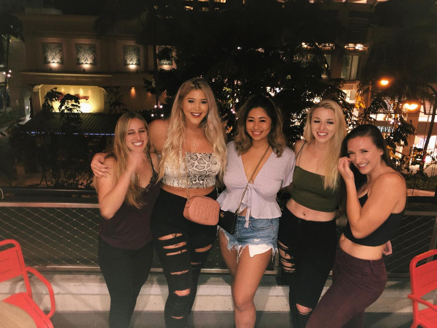 A group of college friends laughing after a night out on the town during spring break in Waikiki.